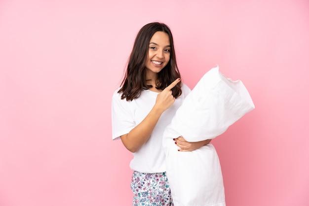 製品を提示する側を指しているピンクで隔離のパジャマの若い女性