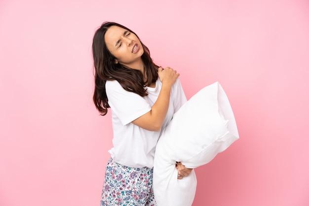 Молодая женщина в пижаме на розовом фоне страдает от боли в плече