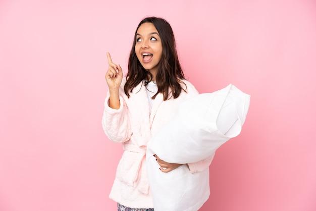 ピンクの壁に隔離されたパジャマの若い女性は、指を持ち上げながら解決策を実現しようとしています