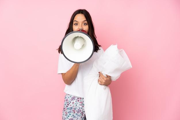 Молодая женщина в пижаме на розовом кричит через мегафон