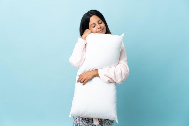잠옷에 격리 된 배경 위에 잠옷에 젊은 여자와 잠자는 동안 베개를 들고