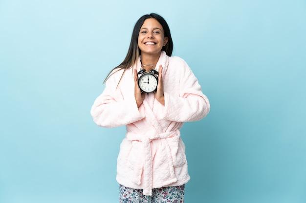 잠옷에 고립 된 이상 잠옷에 젊은 여자와 행복 한 표정으로 시계를 들고