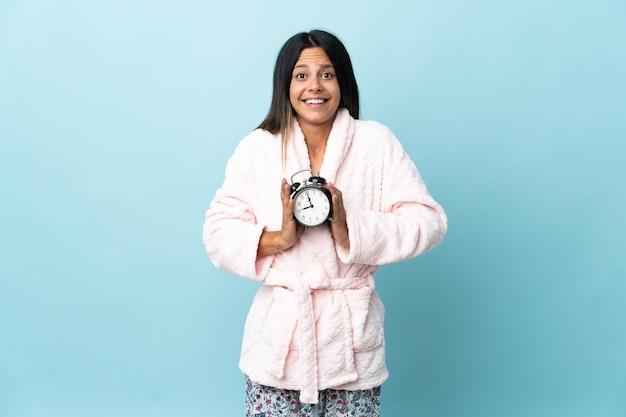 잠옷에 고립 된 벽에 잠옷에 젊은 여자와 놀란 표정으로 시계를 들고