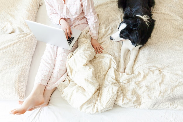 自宅のラップトップを使用して動作しているペットの犬と一緒にベッドの上に座っているパジャマの若い女性