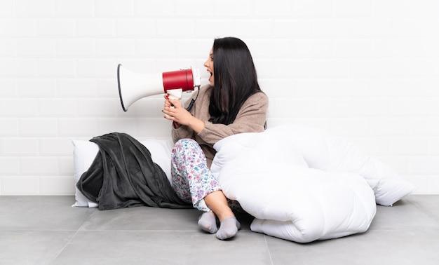 Молодая женщина в пижаме сидит на полу