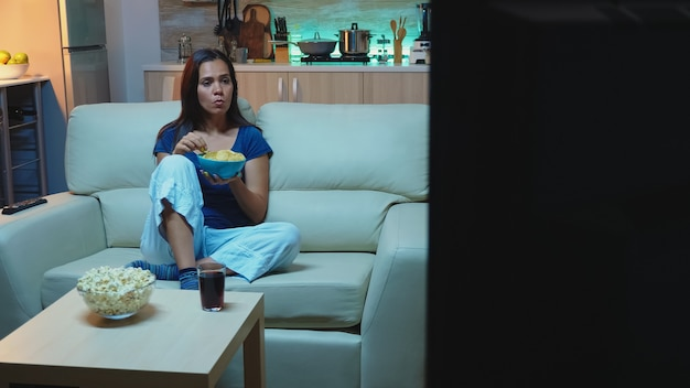 잠옷을 입은 젊은 여성이 밤늦게까지 간식을 먹고 tv를 보고 있습니다. 지루하고 집에 혼자 있는 늦은 밤 아가씨는 그릇을 들고 웃는 편안한 소파에 누워 tv를 보면서 휴식을 취합니다.