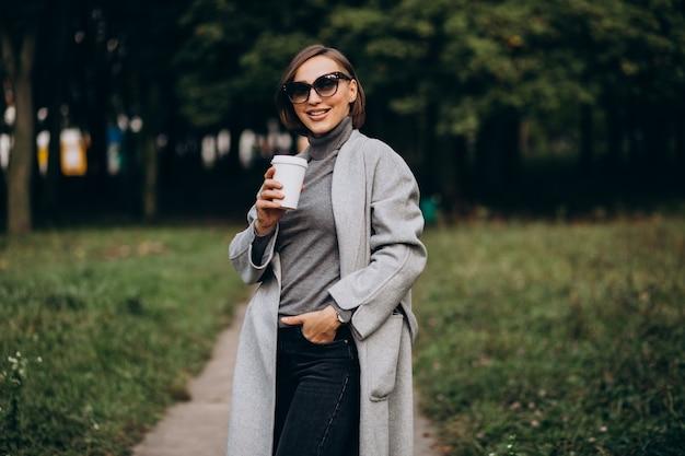 Молодая женщина в парке пьет кофе и разговаривает по телефону