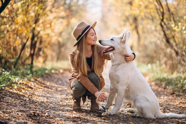 그녀의 하얀 강아지와 함께 공원에서 젊은 여자