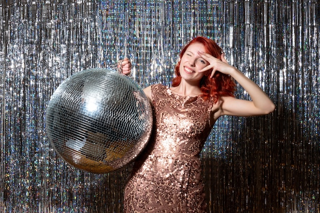 明るいカーテンでディスコボールとパーティーで若い女性