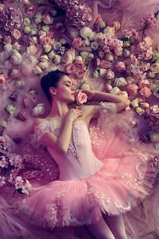 花に囲まれたピンクのバレエチュチュの若い女性