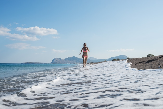 泡の波が入ってくる美しい小石のビーチと一緒に走っているピンクのビキニの若い女性。