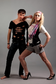 사진 스튜디오에서 gey 배경 위에 뒤에서 검은 색에서 젊은 남자를 껴 안은 분홍색 의류에 젊은 여자. 아름다움과 패션 라이프 스타일 컨셉