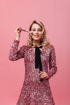 ふわふわ化粧ブラシを保持しているピンクのドレスの若い女性
