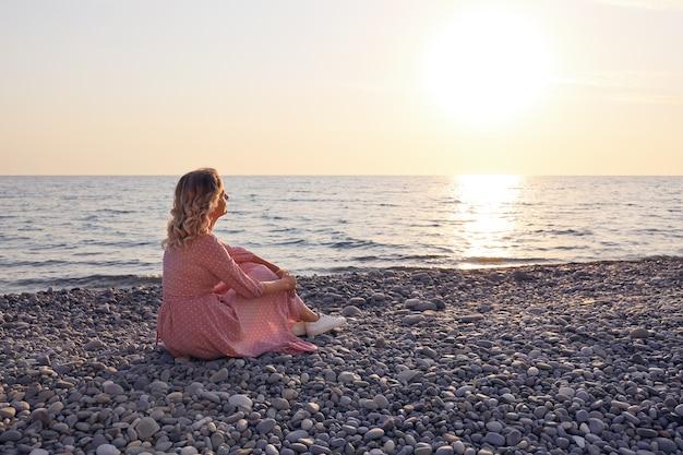 Молодая женщина в розовом платье сидит на гальке на закате и наслаждается одна