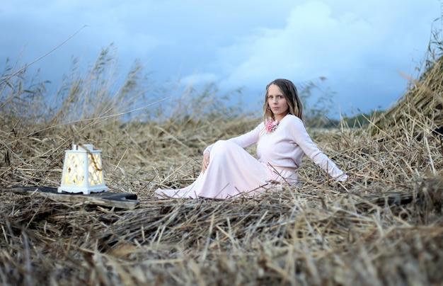 Молодая женщина в розовом длинном платье с фонарем сидит на серой траве