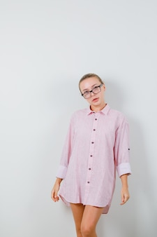ピンクのシャツを着た若い女性、眼鏡をかけて