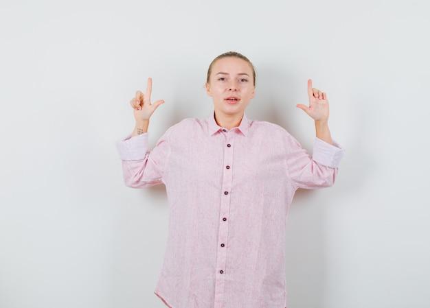 ピンクのシャツを着た若い女性が上を向いて自信を持って見える