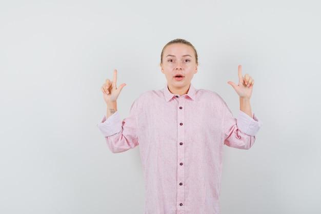 ピンクのシャツを着た若い女性が上を向いて心配そうに見えます