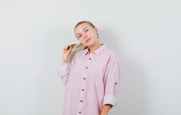 Молодая женщина в розовой рубашке позирует, держа прядь