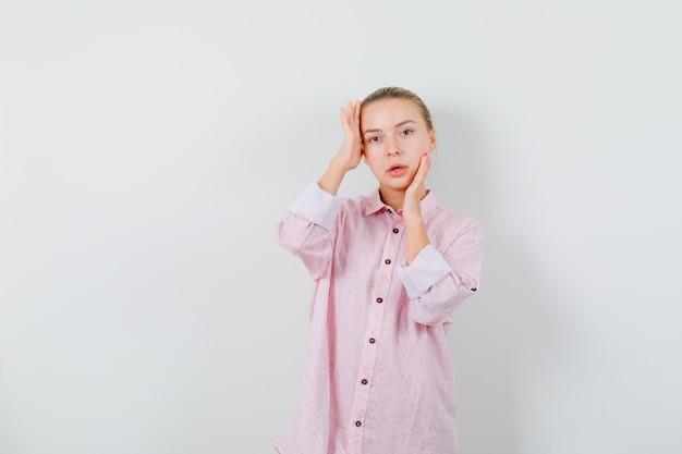 Молодая женщина в розовой рубашке позирует, трогая лицо и очаровательно выглядя