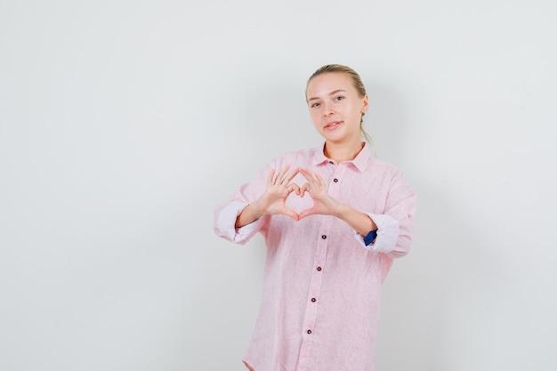 ハートのジェスチャーを示し、陽気に見えるピンクのシャツの若い女性