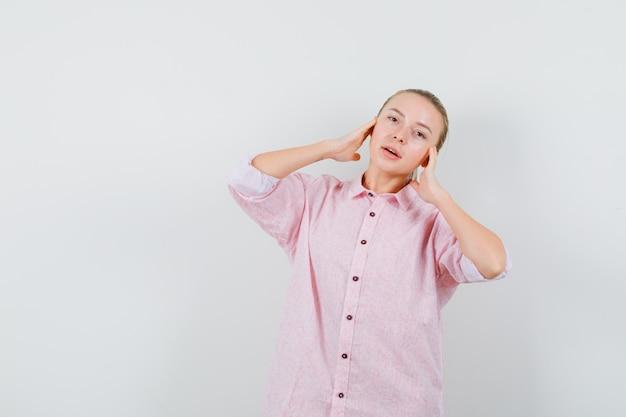 ピンクのシャツを着た若い女性が手で顔に触れ、前向きに見える