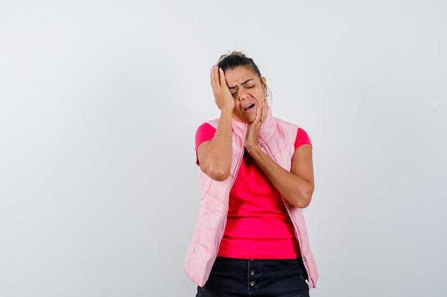 분홍색 티셔츠와 재킷에 젊은 여자가 머리에 손을 넣고 짜증을 찾고