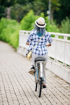 自転車に乗って格子縞のシャツとバケツの帽子の若い女性、後ろからの眺め
