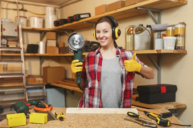格子縞のシャツの灰色のtシャツのノイズ絶縁ヘッドフォン黄色の手袋をはめた若い女性は、木片、さまざまなツール、パワーソーを備えた木製のテーブルの場所で大工仕事のワークショップで働いています。