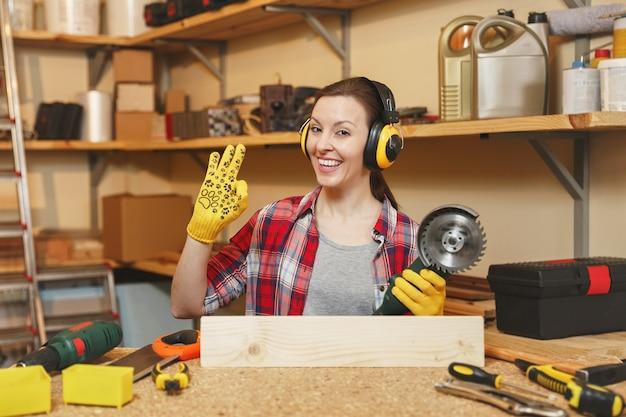 格子縞のシャツの若い女性灰色のtシャツ遮音ヘッドフォン黄色の手袋は、木製のテーブルの場所で大工仕事のワークショップで働いています。