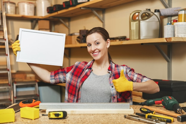Молодая женщина в клетчатой рубашке, серой футболке, желтых перчатках, работающих в столярной мастерской на месте деревянного стола с пустой рамкой, различными инструментами. с пустым местом для текста. скопируйте место для рекламы.