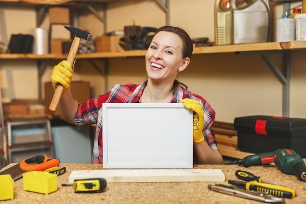 Молодая женщина в клетчатой рубашке, желтых перчатках, работающих в столярной мастерской на месте деревянного стола с молотком, пустой рамкой, различными инструментами. с пустым местом для текста. скопируйте место для рекламы.