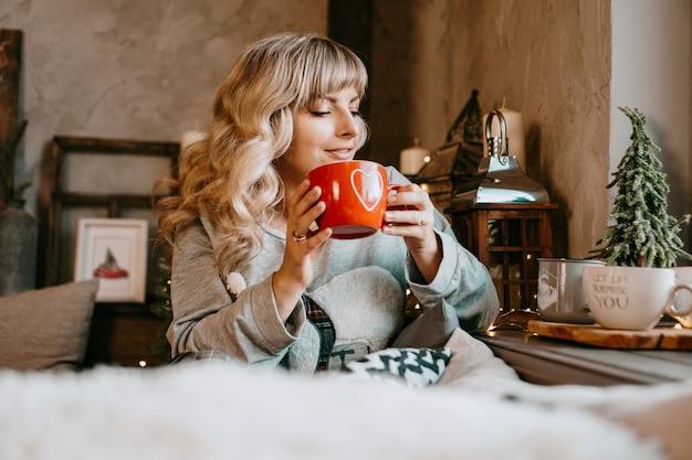 Молодая женщина в пледе с чашкой горячего чая в уютном интерьере рождества. концепция подготовки к праздникам, загадывать желание и мечтать