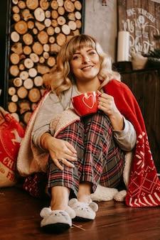 クリスマスの居心地の良いインテリアで熱いお茶のカップと格子縞の若い女性休日の準備の概念願いと夢を作る