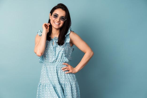 파란색 벽 행복 한 얼굴에 서있는 폴카 도트 드레스에 젊은 여자