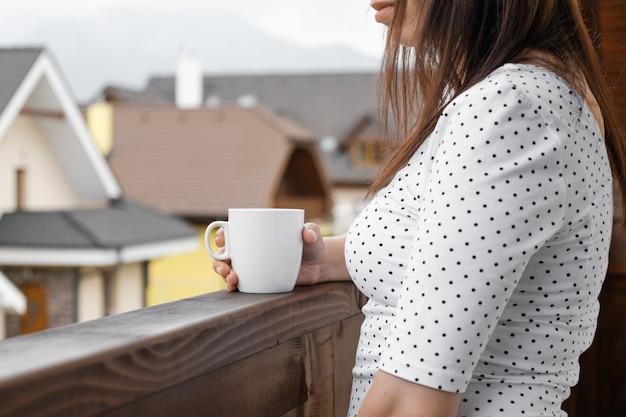 バルコニーに立っている白いお茶やコーヒーと水玉模様のtシャツの若い女性。