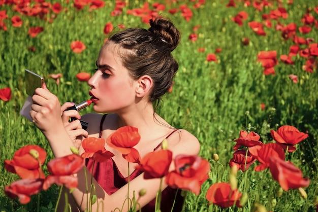 ポピーの花畑、若さと新鮮さの若い女性。きれいな女性の赤い唇が鏡と口紅でメイクアップ