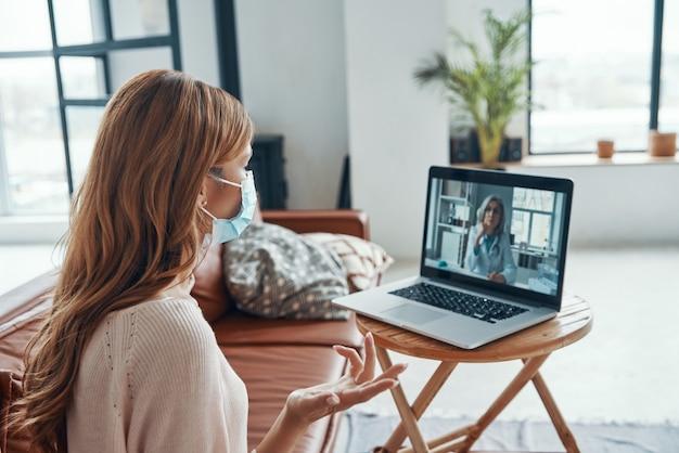Молодая женщина в защитной маске разговаривает с врачом во время видеоконференции на ноутбуке