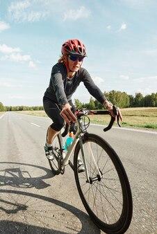 산악 도로에서 자전거를 타고 보호용 헬멧을 쓴 젊은 여성