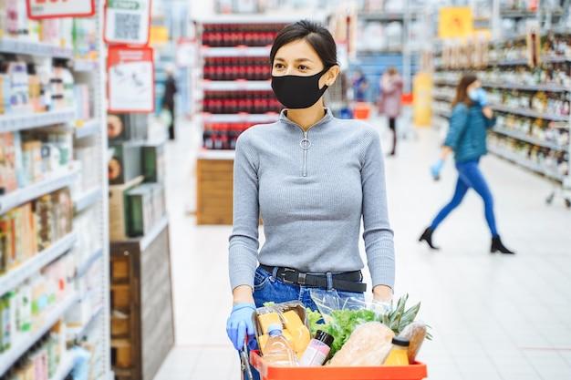 スーパーマーケットで製品を選択する保護マスクと手袋の若い女性。パンデミック時の安全な買い物。