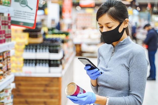 バーコードをスキャンする保護マスクと手袋の若い女性