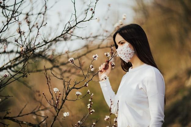 コロナウイルスからの保護マスクの若い女性。