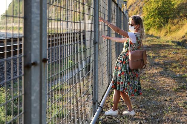 보호 마스크의 젊은 여성이 그녀의 손으로 그릴을 잡고 자유의 길을 막았습니다.