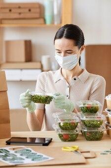 그녀는 음식 배달 서비스에서 일하는 그녀의 손에 야채와 함께 상자를 들고 보호 마스크에 젊은 여자