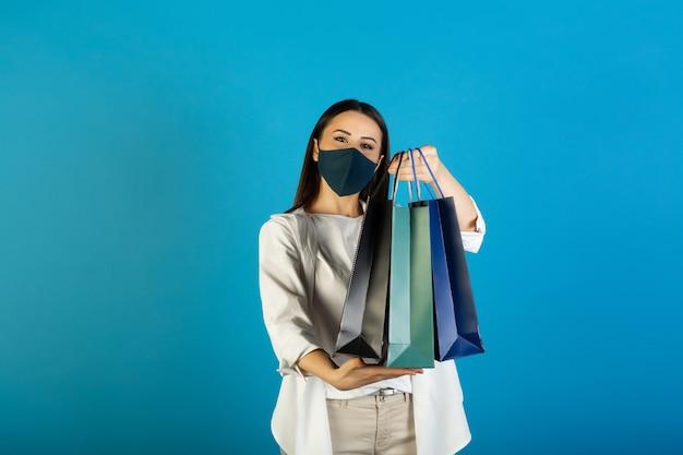 Молодая женщина в защитной маске на лице с красочными бумажными пакетами в руках