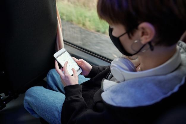 Молодая женщина в защитной маске, прокручивая карту на экране смартфона