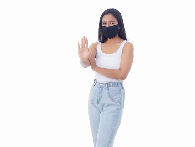白い壁に停止ジェスチャーを示す保護マスクの若い女性