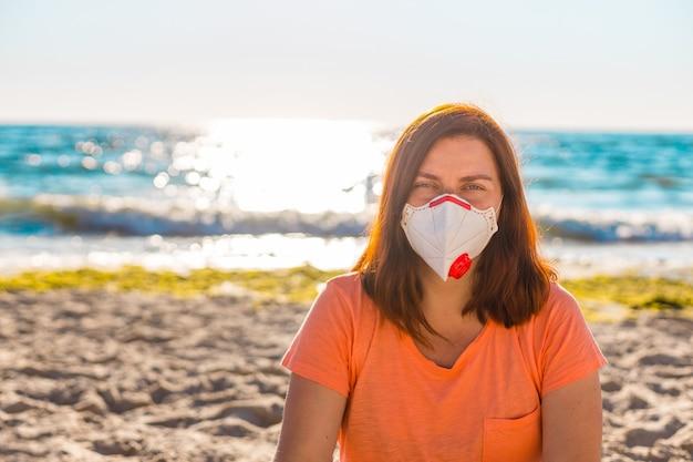 防護マスクの若い女性は海の近くのビーチに座っています。