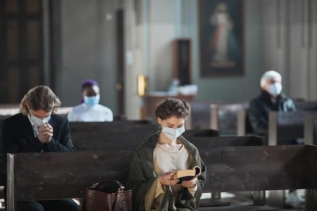 Молодая женщина в защитной маске сидит на скамейке и читает библию в церкви