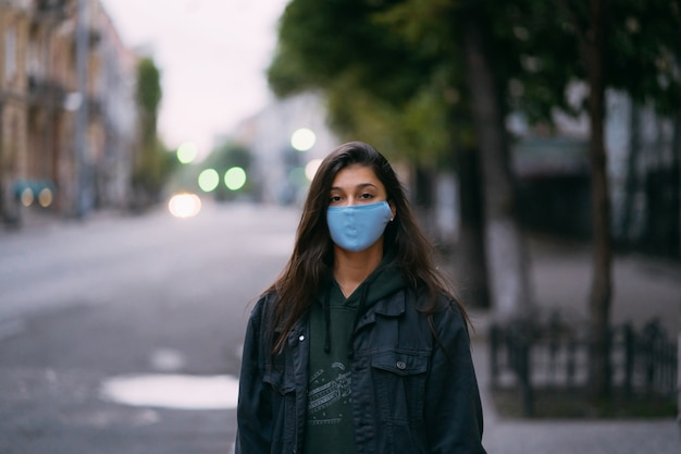 空の通りで防護マスクの若い女性